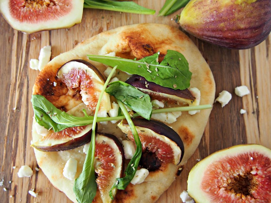 Fresh figs, feta cheese, and spring greens on naan flatbread